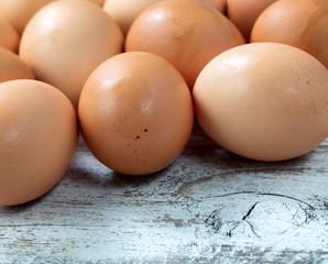 Raw organic brown farm eggs on white rustic wood background
