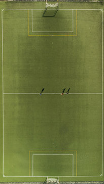 Aerial view of a football training players and shadows on synthetic surface football pitch on a summer day.