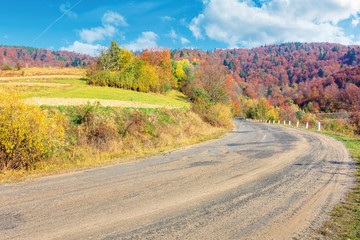 old cracked country road in autumn. traditional carpathian countryside. warm sunny day. trees in colorful foliage. green grass on the rural fields. loacrion Uzhok serpentine, ukraine