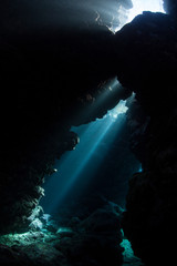 Fototapete - Light descends into the darkness of a submerged cavern in the Solomon Islands. Caves and caverns riddle coral reefs since limestone can be easily eroded.