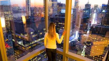 CLOSE UP: Tourist girl stands by the windows and observes the morning cityscape.