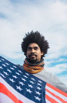 Man with afro hair proudly showing the American flag