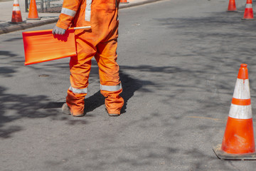 street construction zone with orange suited man directing traffic with orange flag Fotomurales