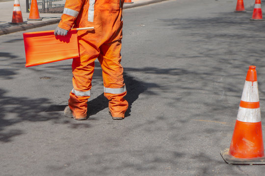 street construction zone with orange suited man directing traffic with orange flag