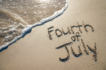 Fourth of July message written for the American Independence Day holiday in smooth sand with incoming wave on the beach