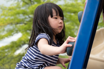 Cute Asian little girl is climbing up on ladder in playground