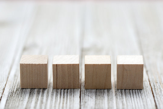 Four wooden toy cubes arranged in row on white grey wooden background