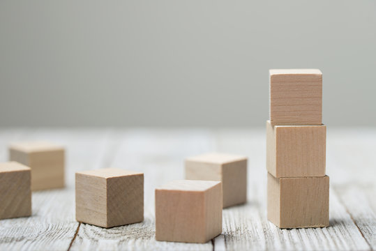 Three wooden toy cubes arranged in vertical on white grey wooden background