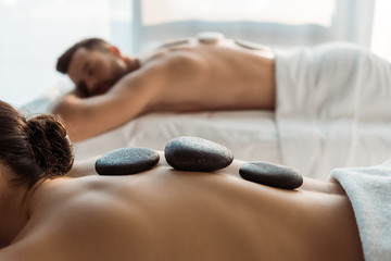 selective focus of woman having stone massage near man in spa center