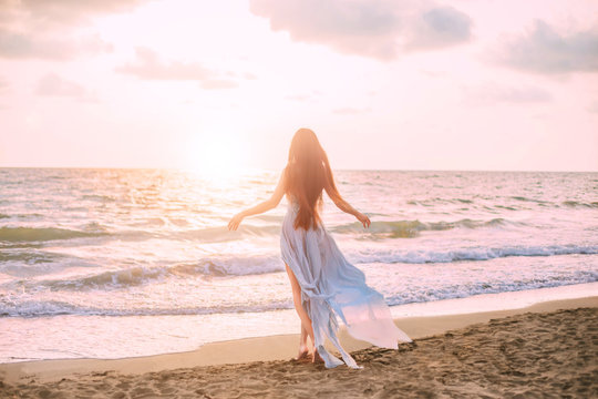 mysterious mermaid with long black hair slowly walks in water of ocean, sea nymph listens to wind like wave in long blue dress with flying train, looks at divine sunset. photo from the back, no face