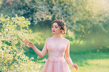 42aabe1fba7c7 charming lady in blooming garden, girl with gathered hair gently strokes  branches of trees with