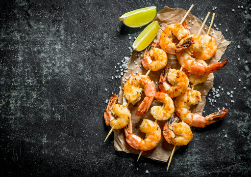Shrimps fried on skewers with slices of lime.