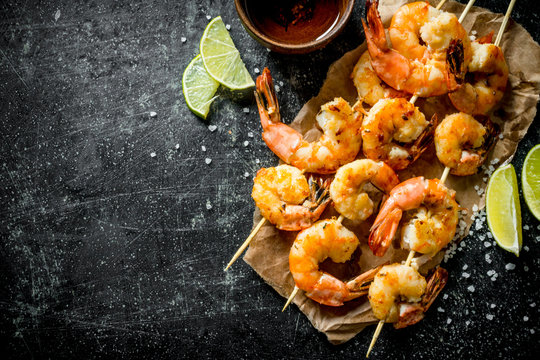 Grilled shrimps on paper with the cut lime.