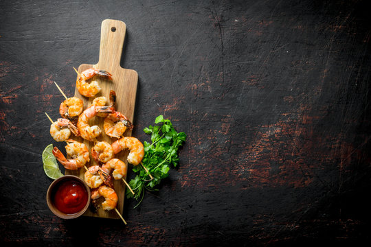 Cooked shrimps on a wooden cutting Board with sauce and herbs.
