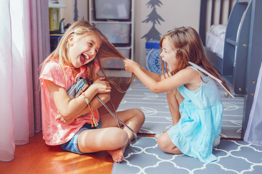 Two little mad angry girls sisters having fight at home. Friends girls can not share toy bag. Lifestyle authentic funny family moment of siblings quarrel. Kids bad behaviour.
