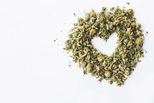 Heart made of crushed up marijuana herb isolated on white background