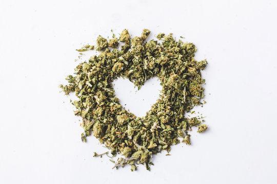 Heart made of crushed up marijuana isolated and centered on white background