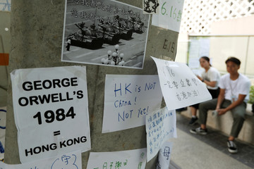 """A placard showing a 1989 photo of """"Tank Man"""" is seen among other notes posted on the wall as people gather near the Legislative Council building to wait for a government announcement regarding the proposed extradition bill, in Hong Kong"""