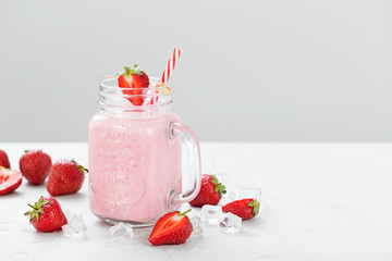Strawberry smoothie or milkshake in mason jar .