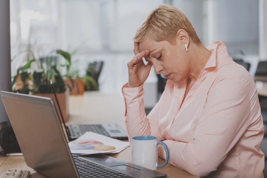 Mature businesswoman looking tired, rubbing her forehead, sitting in front of laptop. Experienced female entrepreneur having headache at work