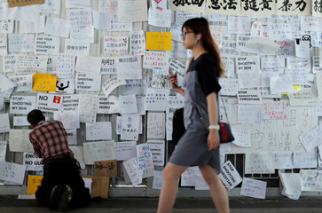 A man sticks notes on the wall near the Legislative Council building, as people gather to wait for a government announcement regarding the proposed extradition bill, in Hong Kong