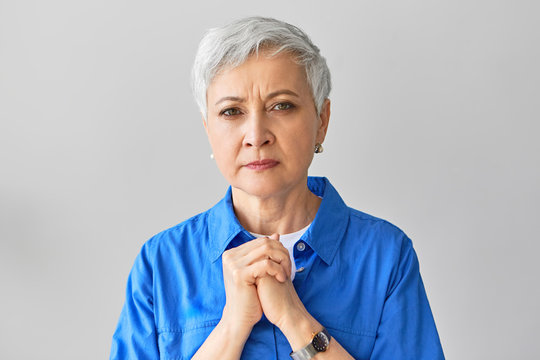 Frustrated worried mature gray haired female holding hands on her chest, having uneasy facial expression, worrying about her husband who is sick. Human emotions, reactions and body language