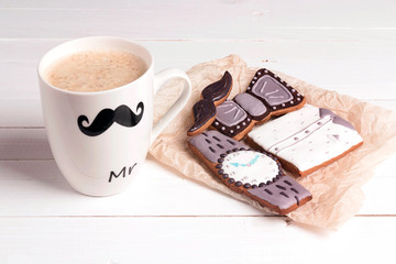 Funny coffee mug with tasty creative cookies on white table.  Father's Day concept.
