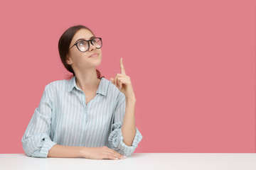 Creative mind, ideas, education and occupation concept. Picture of nerdy smart young Caucasian woman wearing blue shirt and eyeglasses posing at blank pink wall, pointing index finger upwards
