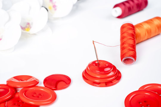 Rote Knöpfe mit Nadel und Faden