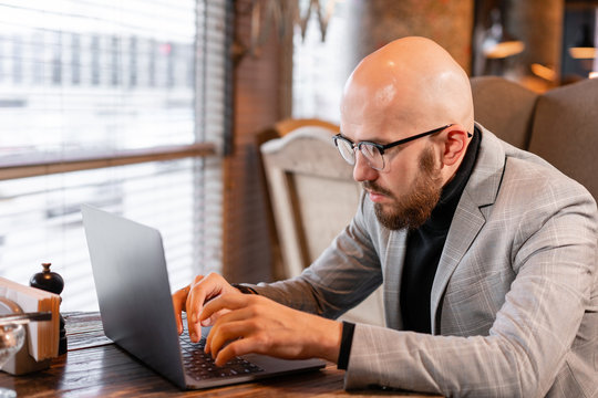 Portrait of young businessman in comfortable cafe. Man with beard in the glasses looking to the monitor laptop. Successful people. Reading text during work on netbook