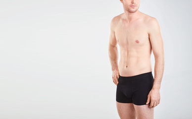 A man in black underwear on a gray background.