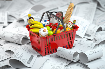 Shopping basket with foods on the pile of receipt.   Consumerism and grocery expenses budget