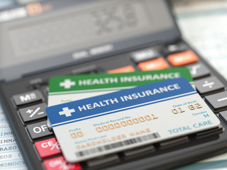 Medical insurance cards on the calculator. Health care costs concept.