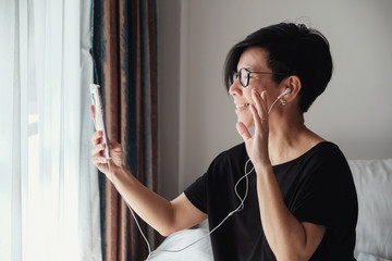 Portrait of  healthy middle aged Asian woman making facetime video calling with  smartphone, using zoom meeting online app, work from home, working remotely, social distancing concept