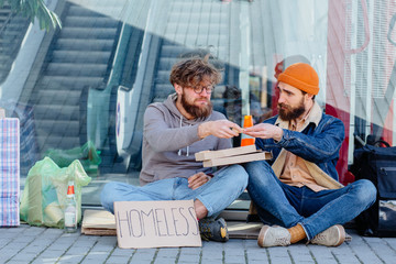 Homeless beggar telling his story young handsome beard man listening with pity compassion emotion sitting together on the ground near shopping mall outdoors. Concept of human understanding