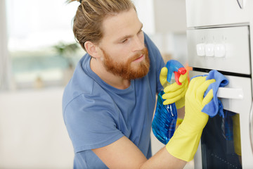 man spraying product to clean oven