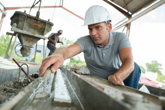 mature worker levelling cement with trowel