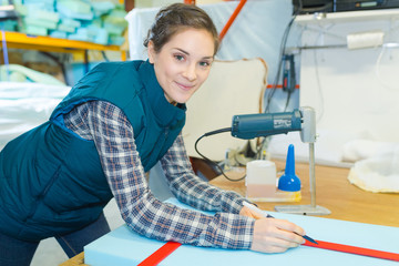 mattress factory worker marking the size