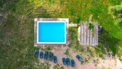 Aerial view of a blue pool with stairs to descend and climb into the water. Around marble tiles. There are empty loungers by the pool. The pool is part of a private villa.