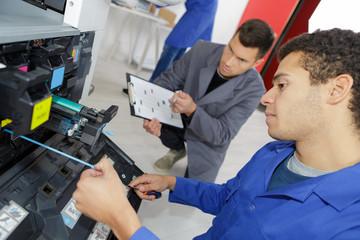 man repairing printer in professional school