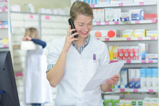 female pharmacist on the phone at the hospital pharmacy