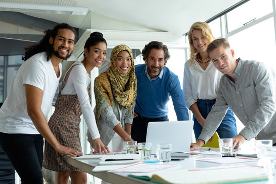 Business people looking at camera while working together at conference room in a modern office