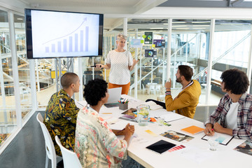 Businesswoman giving presentation on screen during meeting in a modern office