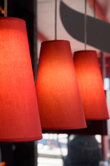 Red lampshades over the table in the cafe