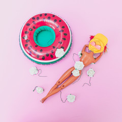 Girl in bikini with white flowers and yellow hat sunbathing on pink beach sand near the inflatable rubber ring in the shape of watermelon. Tropical party. Flat lay, aerial view