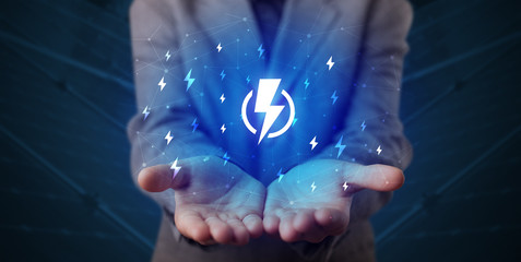 Hand in suit holding lightning bolt on his hand, green environment concept