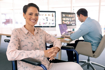 Disabled female graphic designer looking at camera in a modern office