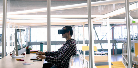 Male graphic designer using virtual reality headset while working on computer at desk