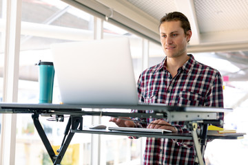 Male graphic designer working on laptop at desk