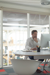 Business male executive working on computer at desk in a modern office